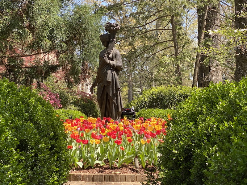 yellow and red tulips around a statue